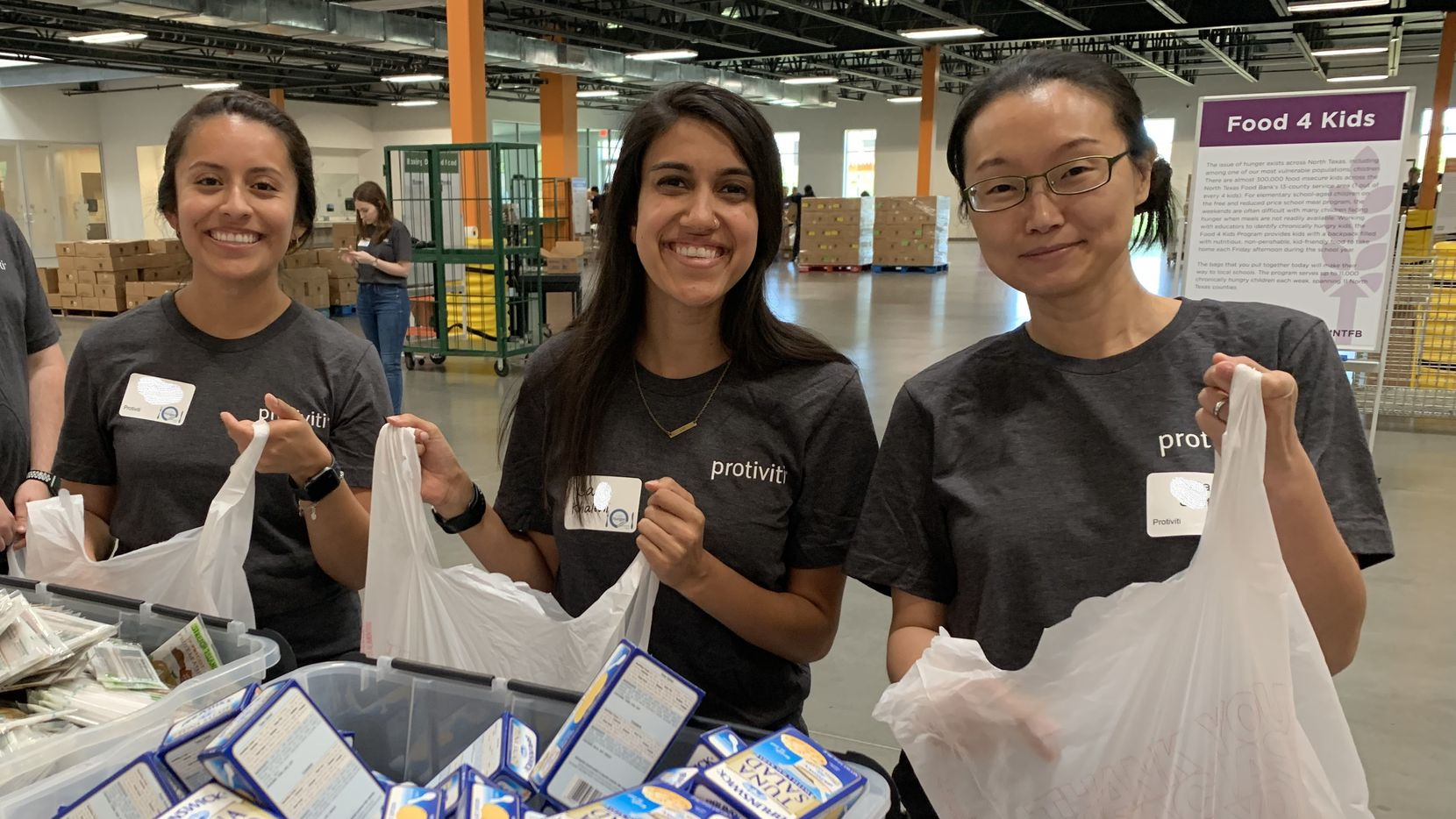 """Protiviti Dallas employees pack meals at a recent event as part of its """"i on Hunger"""" program."""