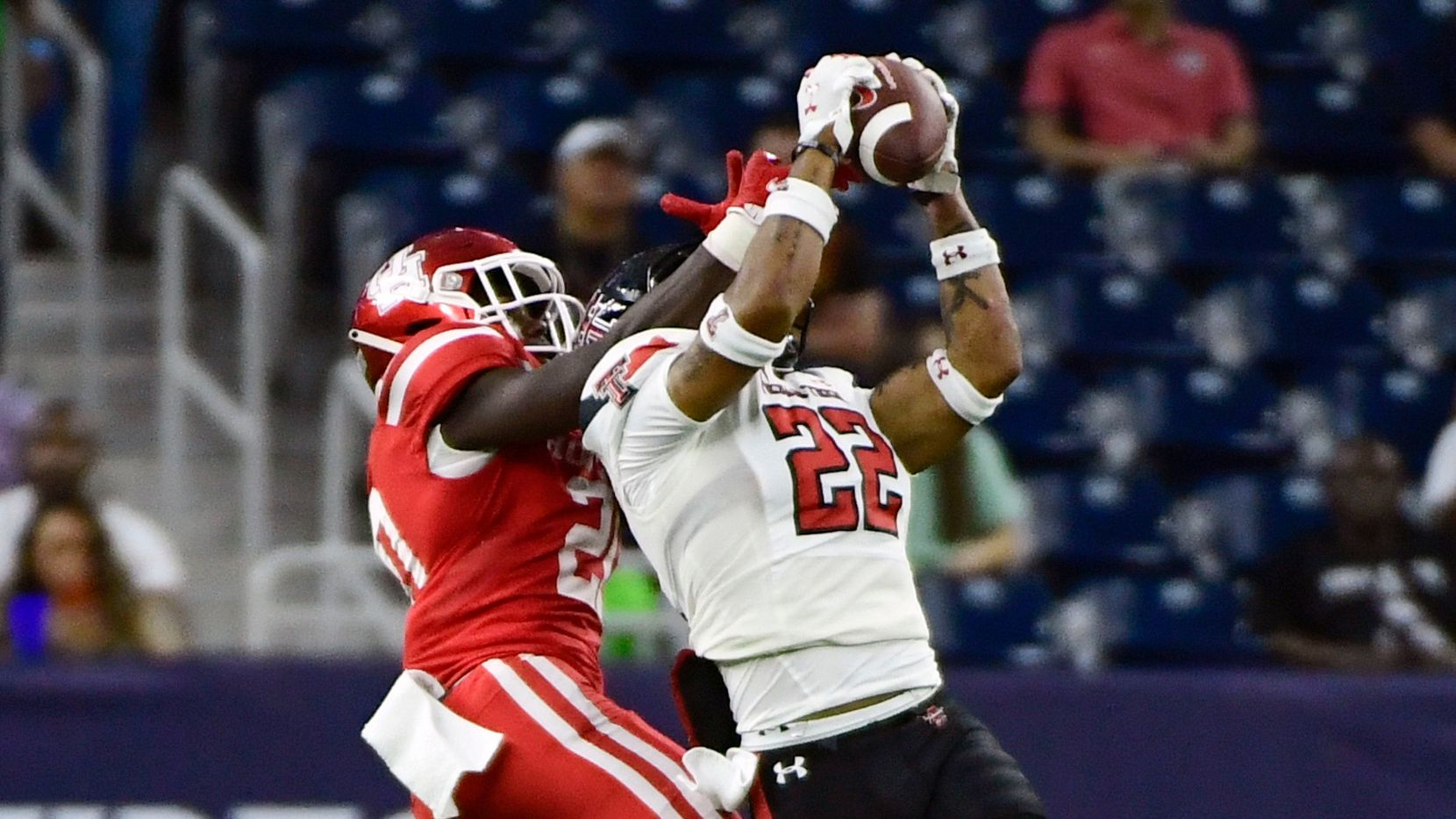 Texas Tech defensive back Reggie Pearson Jr. (22) intercepts a pass under Houston wide receiver KeSean Carter (20) from Houston quarterback Clayton Tune during the first half of an NCAA college football game Saturday, Sept. 4, 2021, in Houston.