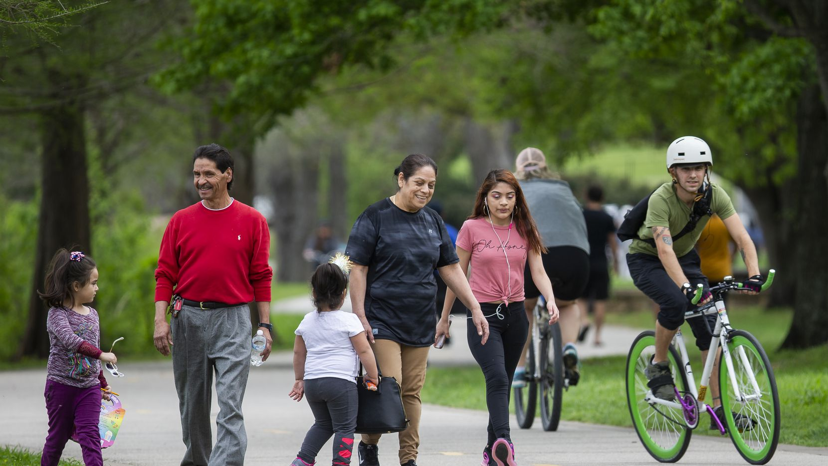 People ride bikes and walk at White Rock Lake on March 29, 2020 in Dallas.