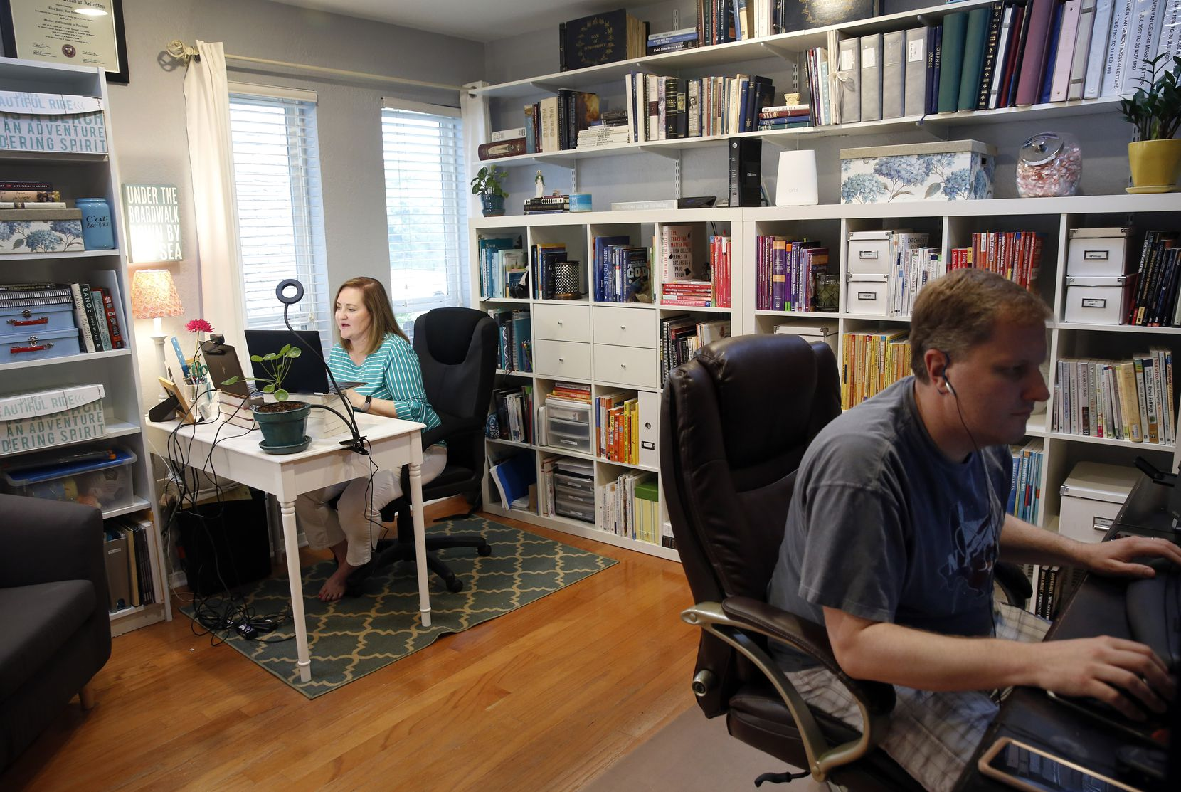 Lisa Van Gemert (left), a former Martin High assistant principal and Lamar High teacher, who now trains teachers, receives technical help from her husband, Steven Van Gemert, as she delivers her live, daily English class on YouTube from their north Arlington home, Tuesday March 17, 2020.