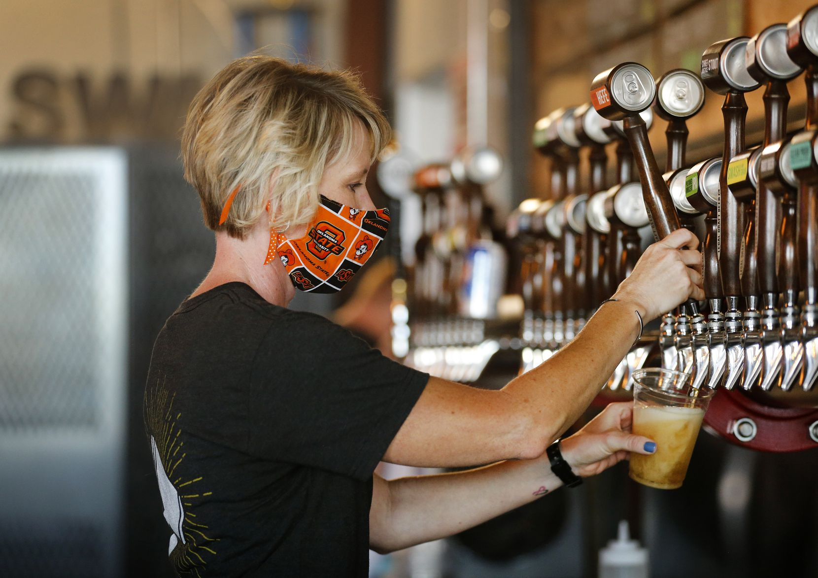 Bartender Rae Huffstetter donned an Oklahoma State University-themed mask while drawing taps at Legal Draft Company.