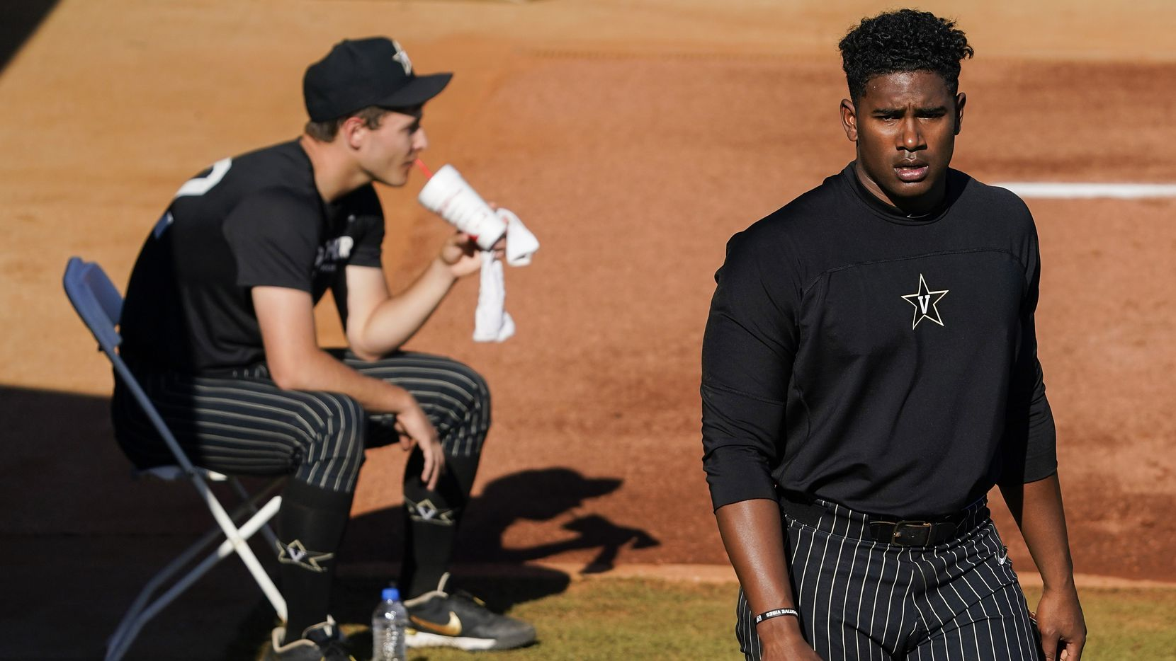 Vanderbilt pitcher Kumar Rocker warms up as fellow pitcher Jack Leiter sips a smoothie in the bullpen before an NCAA baseball game against Mississippi at Swayze Field on Friday, May 14, 2021, in Oxford, Miss.