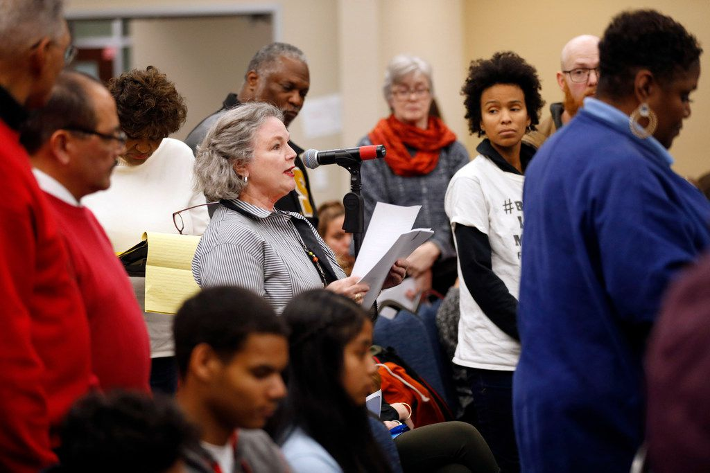 People stand in support of Susybelle Gosslee of Dallas on Thursday. She was, one of nearly 60 people who attended Thursday's Dallas ISD trustee meeting at the Turney W. Leonard Governance and Training Center in Dallas. Many were there to raise objections to the district's plan to open charter schools for pre-k students.