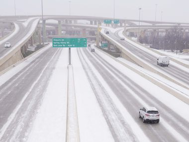 Traffic moves through snow on US-75 near the High Five interchange as a winter storm brings snow and freezing temperatures to North Texas on Sunday, Feb. 14, 2021, in Dallas.  A winter storm watch has been issued for all of North Texas, including Dallas, Denton, Collin and Tarrant counties and will be in effect from late Saturday through Monday afternoon.