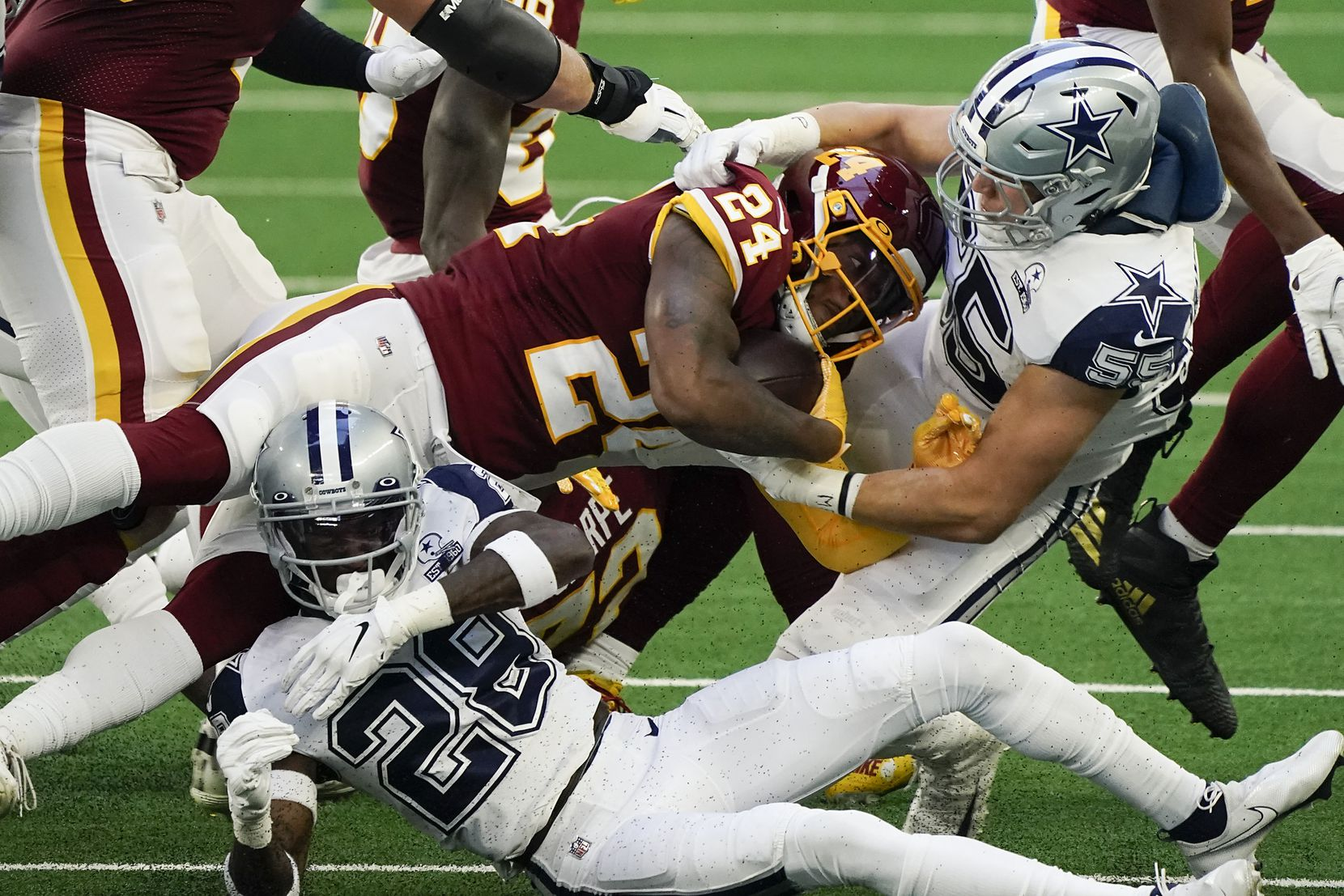 Washington Football Team running back Antonio Gibson (24) is brought down by Dallas Cowboys outside linebacker Leighton Vander Esch (55) and defensive back Rashard Robinson (28) during the first quarter of an NFL football game at AT&T Stadium on Thursday, Nov. 26, 2020, in Arlington. (Smiley N. Pool/The Dallas Morning News)