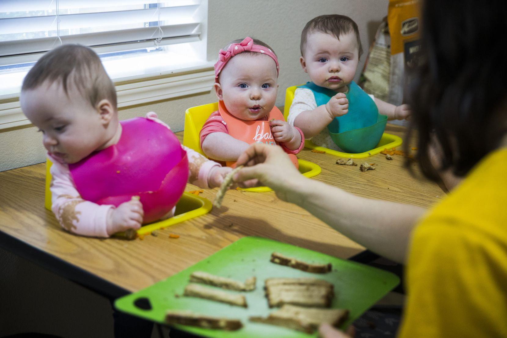 Actress Allison Pistorius (right) feeds her triplets (from left) Austen Finch Pistorius Hury, Birdie Sue Pistorius Hury and Charlie Faye Pistorius Hury, who share slices of toast with hummus on Wednesday, October 9, 2019. Pistorius, who had triplets 11 months ago, is playing the part of Dracula at Theatre Three in Dallas.