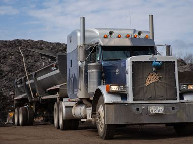 A truck begins hauling off a small piece of Shingle Mountain at Blue Star Recycling off South Central Expressway on Thursday.