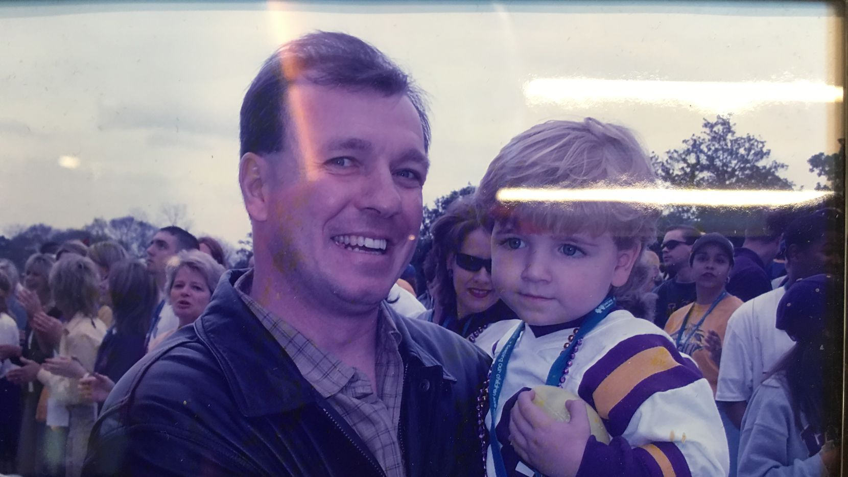 A framed photo behind Fisher's Texas A&M office desk. In the photo Fisher is holding oldest son Trey during LSU's 2003 national championship parade, when Jimbo was a Tigers assistant under Nick Saban. Trey now is a junior quarterback at Godby High School in Tallahassee.