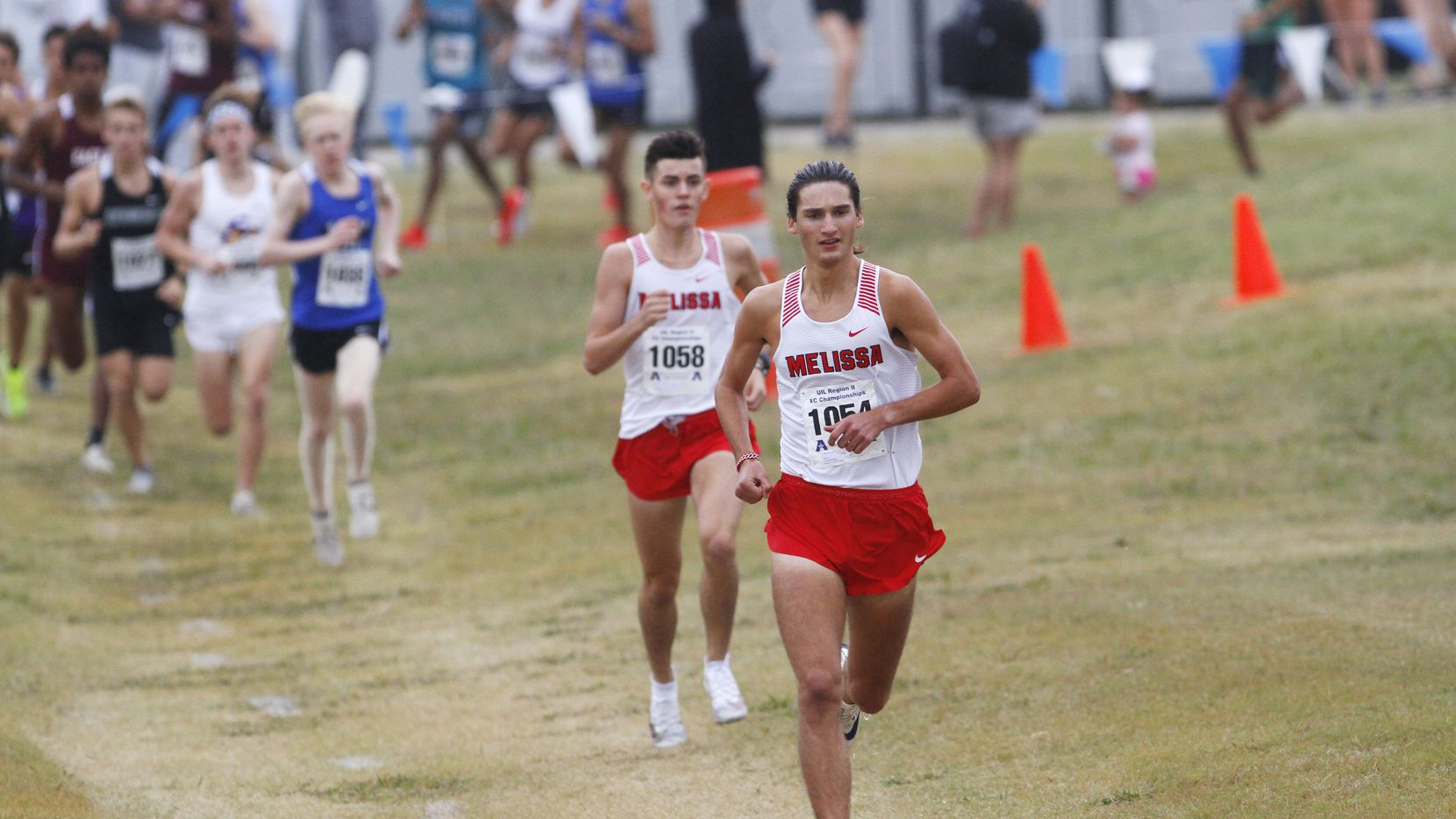 Melissa's Judson Greer (1054) leads the pack, with teammate Lucas Tauch (1058) right behind, during the Class 4A boys race at the Region II cross country meet at Jesse Owens Memorial Complex in Dallas on Tuesday. Greer finished first, and Tauch was second.