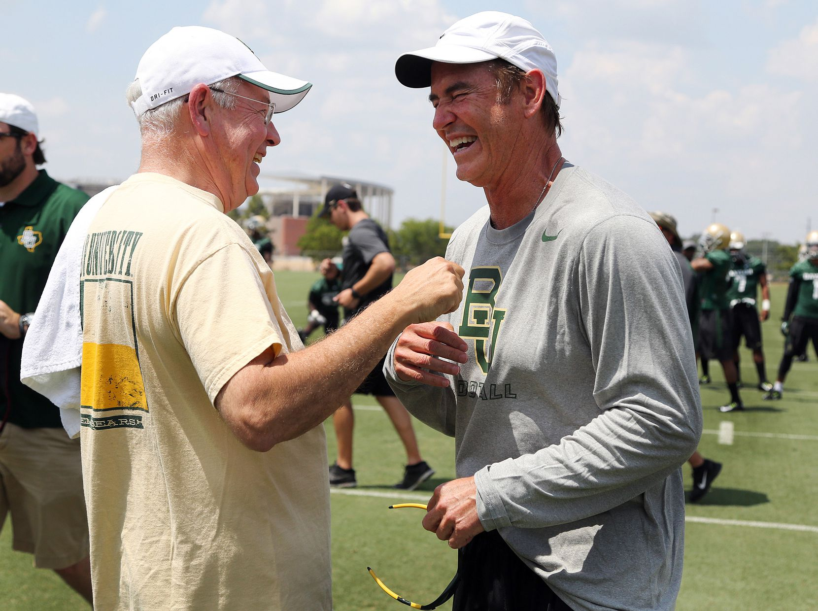 Baylor University President Ken Starr (left) joked with head football coach Art Briles on the first day of NCAA college football practice in 2014. Two years later, both of them were gone amid a sexual-violence scandal involving their football players.