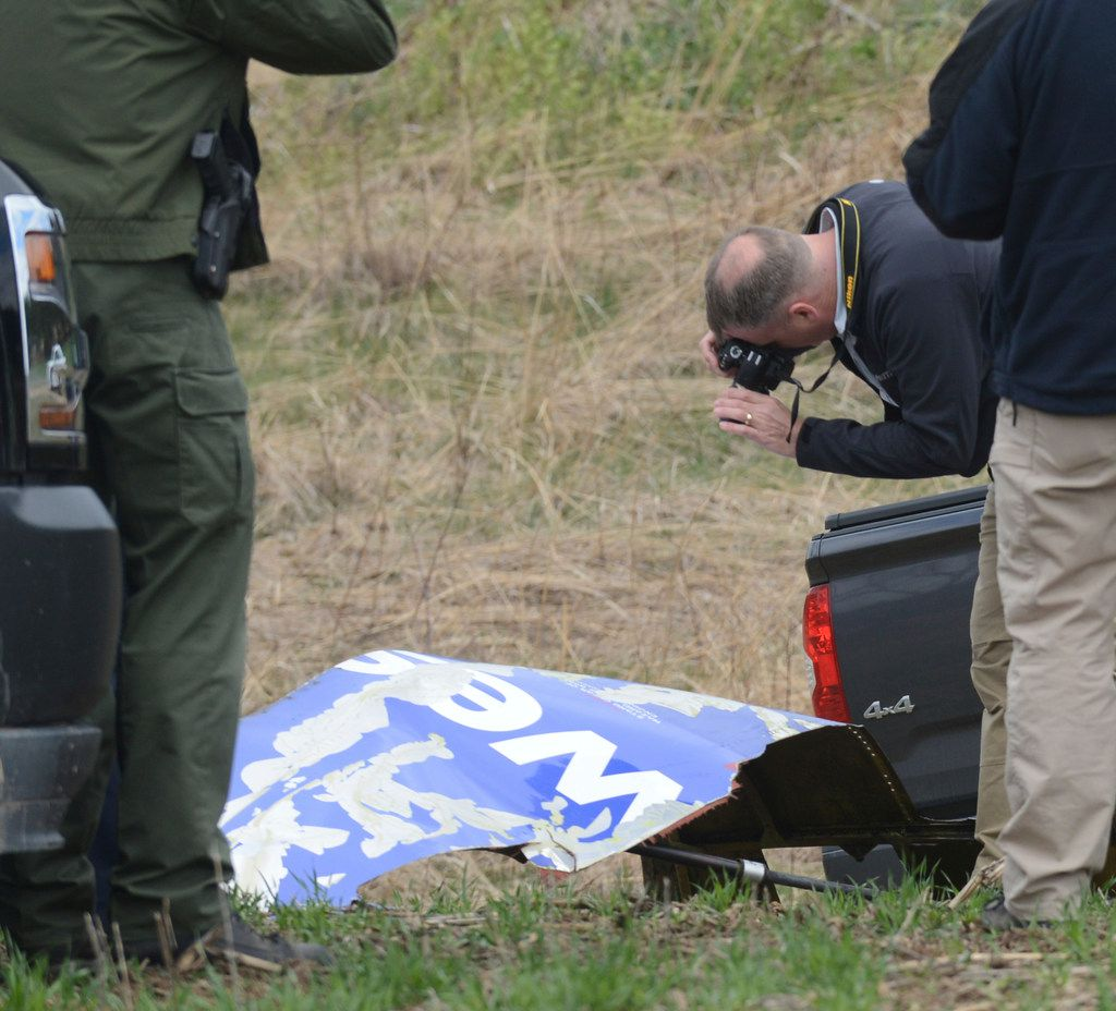 A National Transportation Safety Board investigator photographs a Southwest Airline engine covering that landed in Penn Township, Berks County field from a plane that made an emergency landing Tuesday after a fatal engine mishap, Wednesday, April 18, 2018, on state game lands. (Bill Uhrich/Reading Eagle via AP)