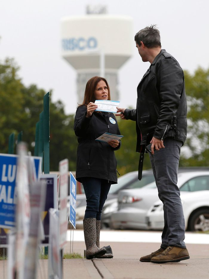 Sherrie Salas, of Frisco talks about the Frisco ISD Bond & TRE with a voter (declined to give his name) outside of a polling station at Collin College Preston Ridge Campus in Frisco on Thursday, October 25, 2018. (Vernon Bryant/The Dallas Morning News)