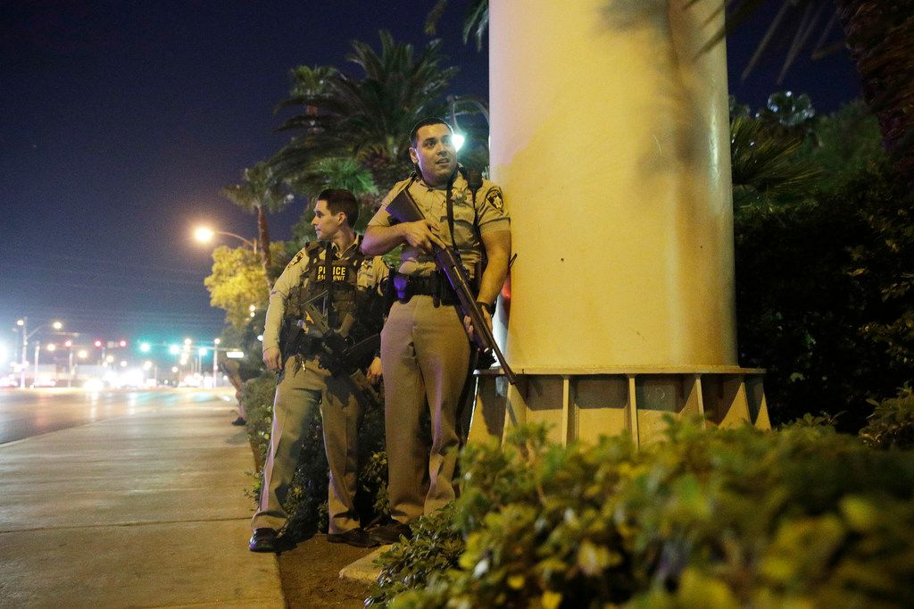 Police take cover near the scene of a shooting close to the Mandalay Bay resort and casino on the Las Vegas Strip.