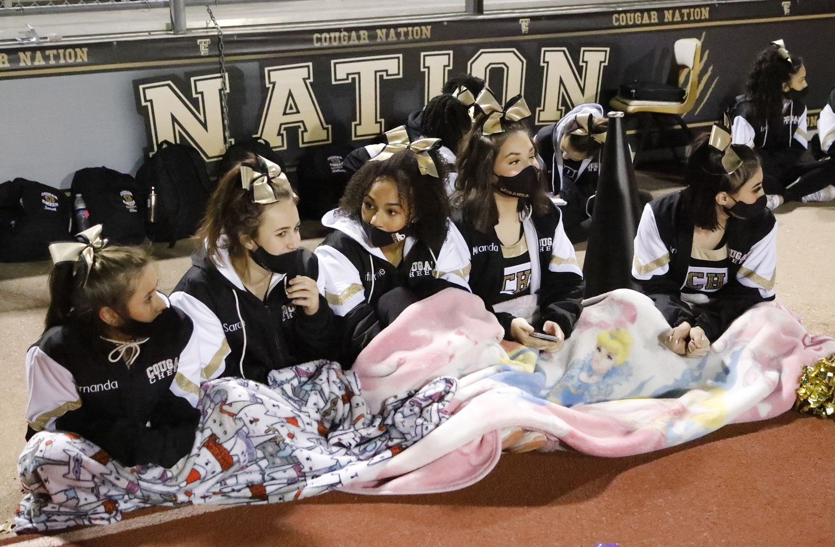 The Colony High School cheerleaders huddle for warmth before kickoff  as The Colony High School hosted Frisco Reedy High School at Tommy Briggs Stadium on Friday night, December 4, 2020.  (Stewart F. House/Special Contributor)