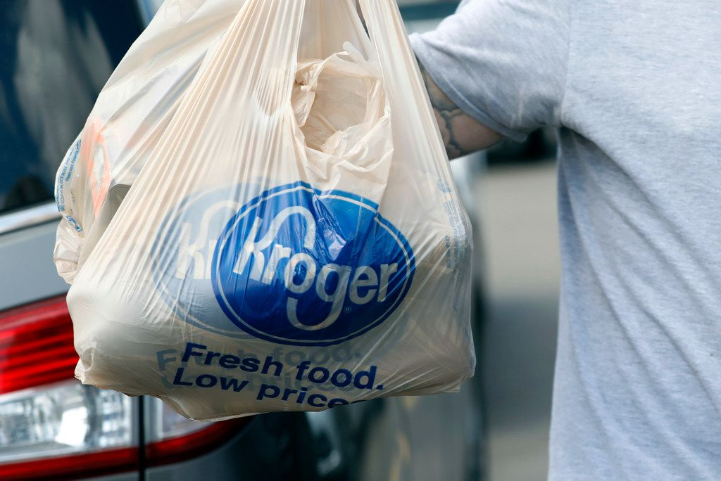 In this Thursday, June 15, 2017, photo, a shopper removes grocery store bags from their shopping cart at a Kroger store in Flowood, Miss. The Kroger Co. reports earnings Thursday, Nov. 30, 2017. (AP Photo/Rogelio V. Solis)