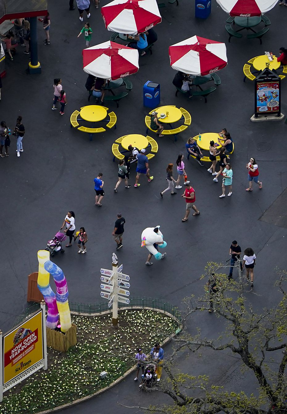 Park visitors walk near a food concession at Six Flags Over Texas on Thursday, March 12, 2020, in Arlington, Texas.