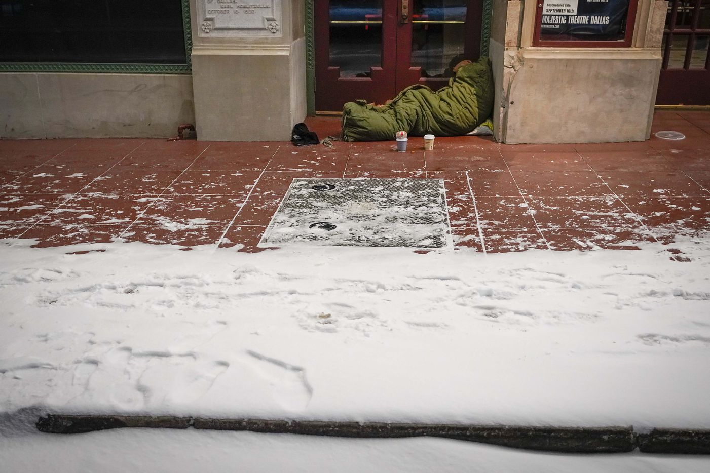 With temperatures already falling into the single digits homeless person sleeps in the doorway of the Majestic Theater as a winter storm brings snow and freezing temperatures to North Texas on Sunday, Feb. 14, 2021, in Dallas.