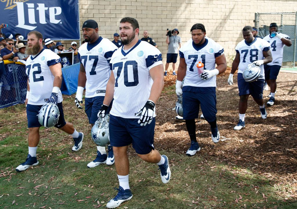 Dallas Cowboys center Travis Frederick (72), Dallas Cowboys tackle Tyron Smith (77), Dallas Cowboys guard Zack Martin (70), Dallas Cowboys offensive guard La'el Collins (71) make their way to the field for the afternoon practice at training camp in Oxnard, California on Monday, July 24, 2017.