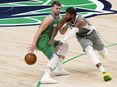 Dallas Mavericks guard Luka Doncic (77) dribbles behind the back to beat LA Clippers guard Paul George for a basket during the second half of an NBA basketball game at American Airlines Center on Wednesday, March 17, 2021, in Dallas.