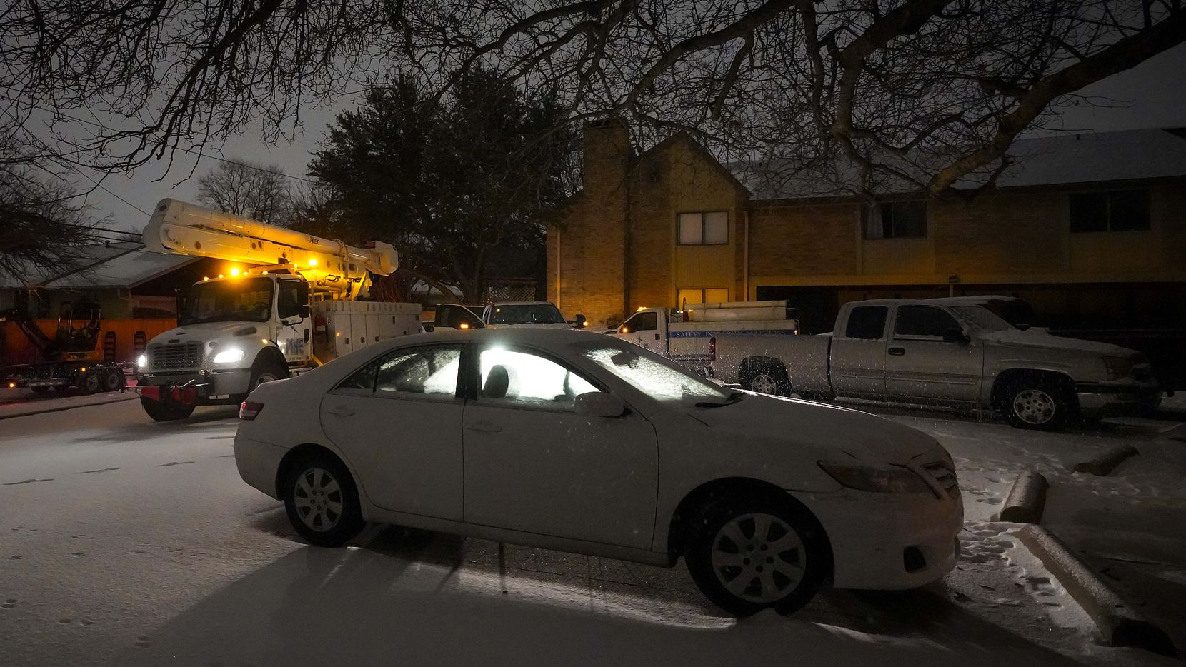 Power crews work in a darkened apartment complex after a second winter storm brought more snow and continued freezing temperatures, and continuing power outages, to North Texas on Tuesday, Feb. 16, 2021, in Richardson.