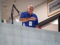Texas Rangers public address announcer Chuck Morgan places his hand over his heart from his booth during a ceremony commemorating his 3000th consecutive game after the fifth inning between the Texas Rangers and the Houston Astros at Globe Life Field on Saturday, Sept. 26, 2020.