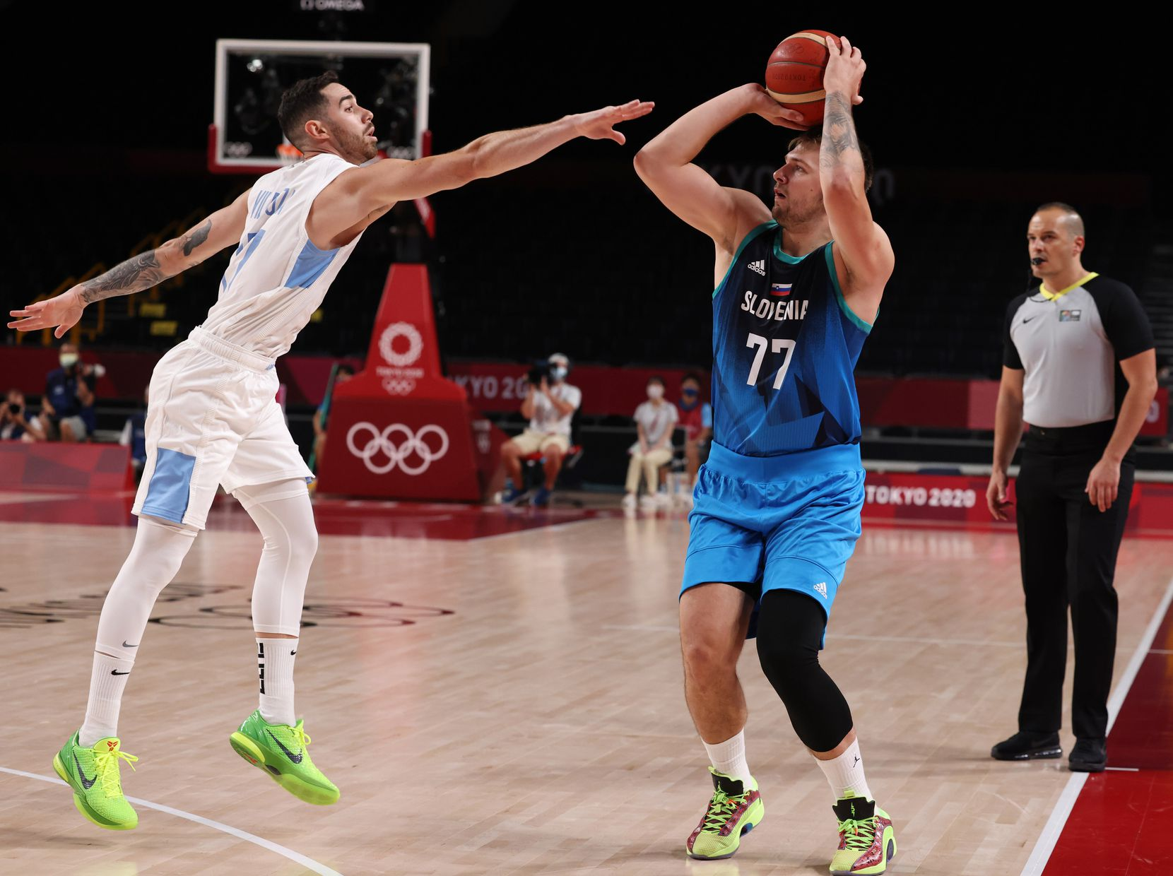 Slovenia's Luka Doncic (77) shoots a three over Argentina's Luca Vildoza (17) in the first half of play during the postponed 2020 Tokyo Olympics at Saitama Super Arena on Monday, July 26, 2021, in Saitama, Japan. Slovenia defeated Argentina 118-100. (Vernon Bryant/The Dallas Morning News)