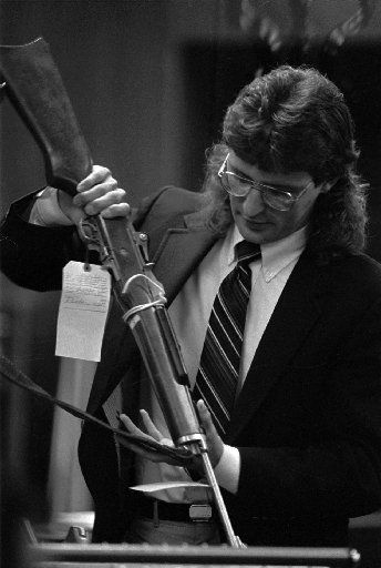 David Koresh during a 1988 court appearance with one of the weapons used in a 1987 shootout at the compound between sect members.