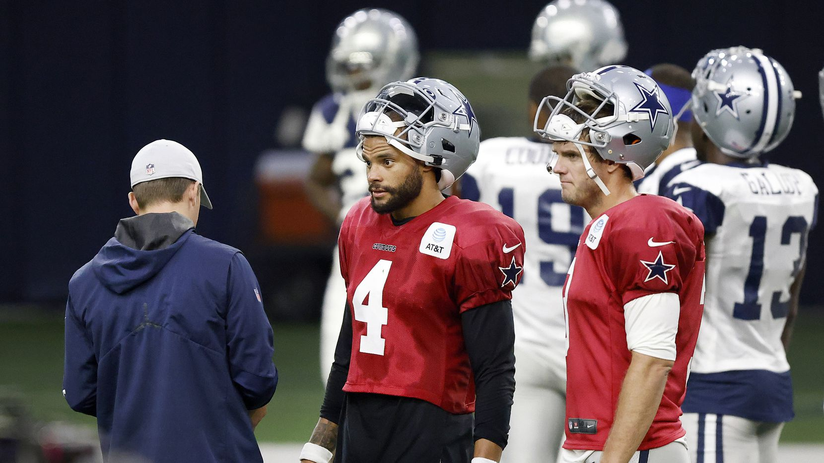 Dallas Cowboys quarterback Dak Prescott (4) visits with offensive coordinator Kellen Moore (left) as he and fellow quarterback Garrett Gilbert (3) wait their turn to play during Training Camp practice at The Star in Frisco, Texas, Wednesday, August 18, 2021.