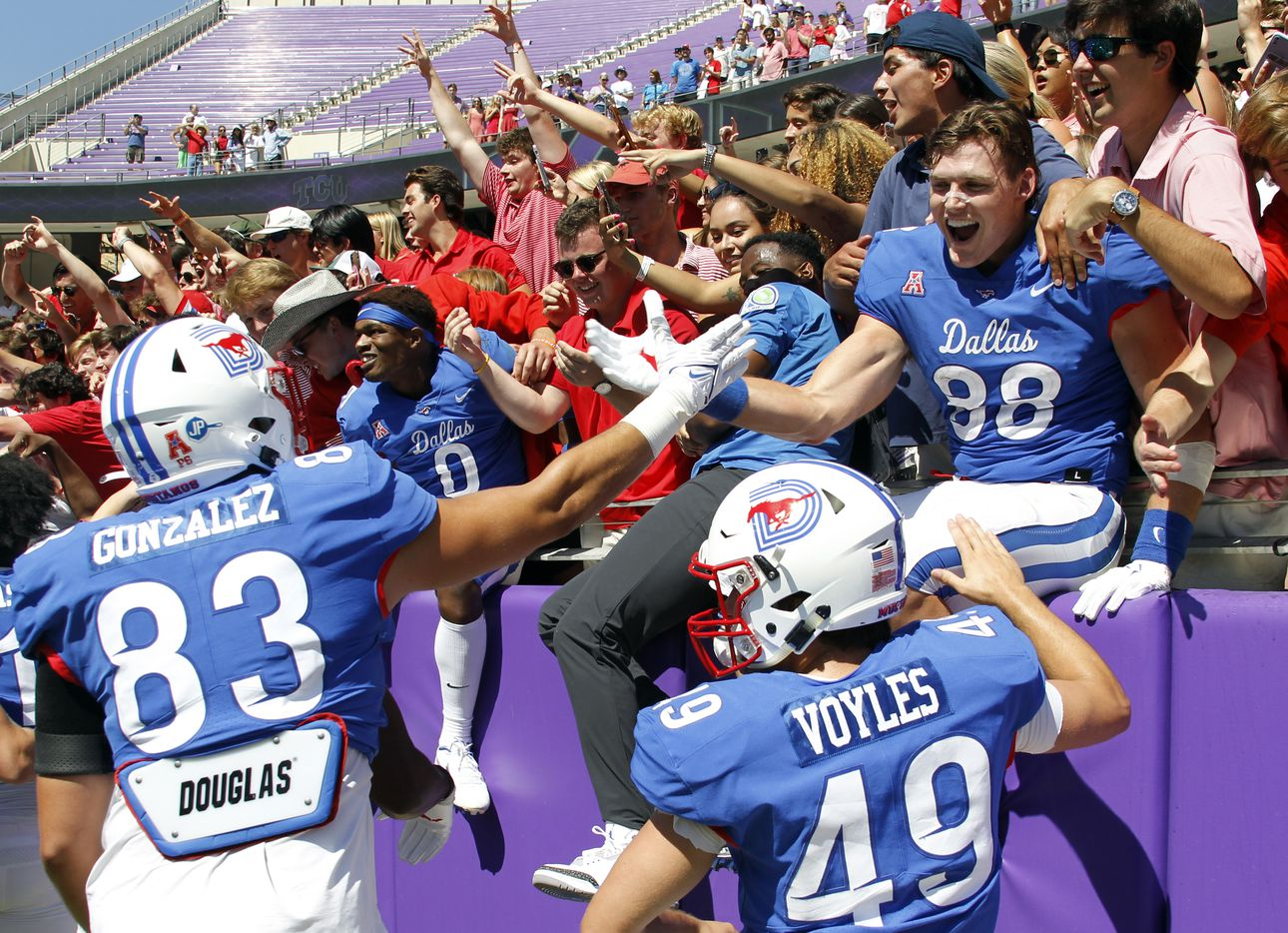 SMU tight end Grant Calcaterra (88), upper right, was all smiles as he shares a congratulatory handshake with teammate Simon Gonzalez (83) as players and fans celebrated the Mustangs' 42-34 victory over TCU. The two teams played their NCAA football game at Amon G. Carter Stadium on the campus of TCU in Fort Worth on September 25, 2021. (Steve Hamm/ Special Contributor)