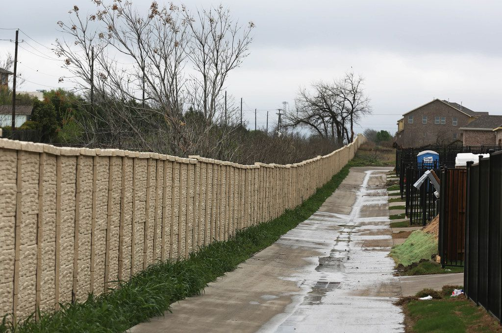 A fence lines the alley separating the University Place subdivision from the easement for railroad tracks at the Cotton Belt crossing near Coit Road in North Dallas. While only about a quarter of the planned commuter rail line is in Dallas, much of the line's impact would be to Dallas neighborhoods. (Louis DeLuca/The Dallas Morning News)