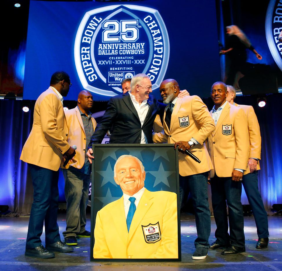Dallas Cowboys owner Jerry Jones (center) gives a big hug to Emmitt Smith after a painted portrait of the newest Cowboys NFL Hall of Famer was given to him. (Tom Fox/The Dallas Morning News)