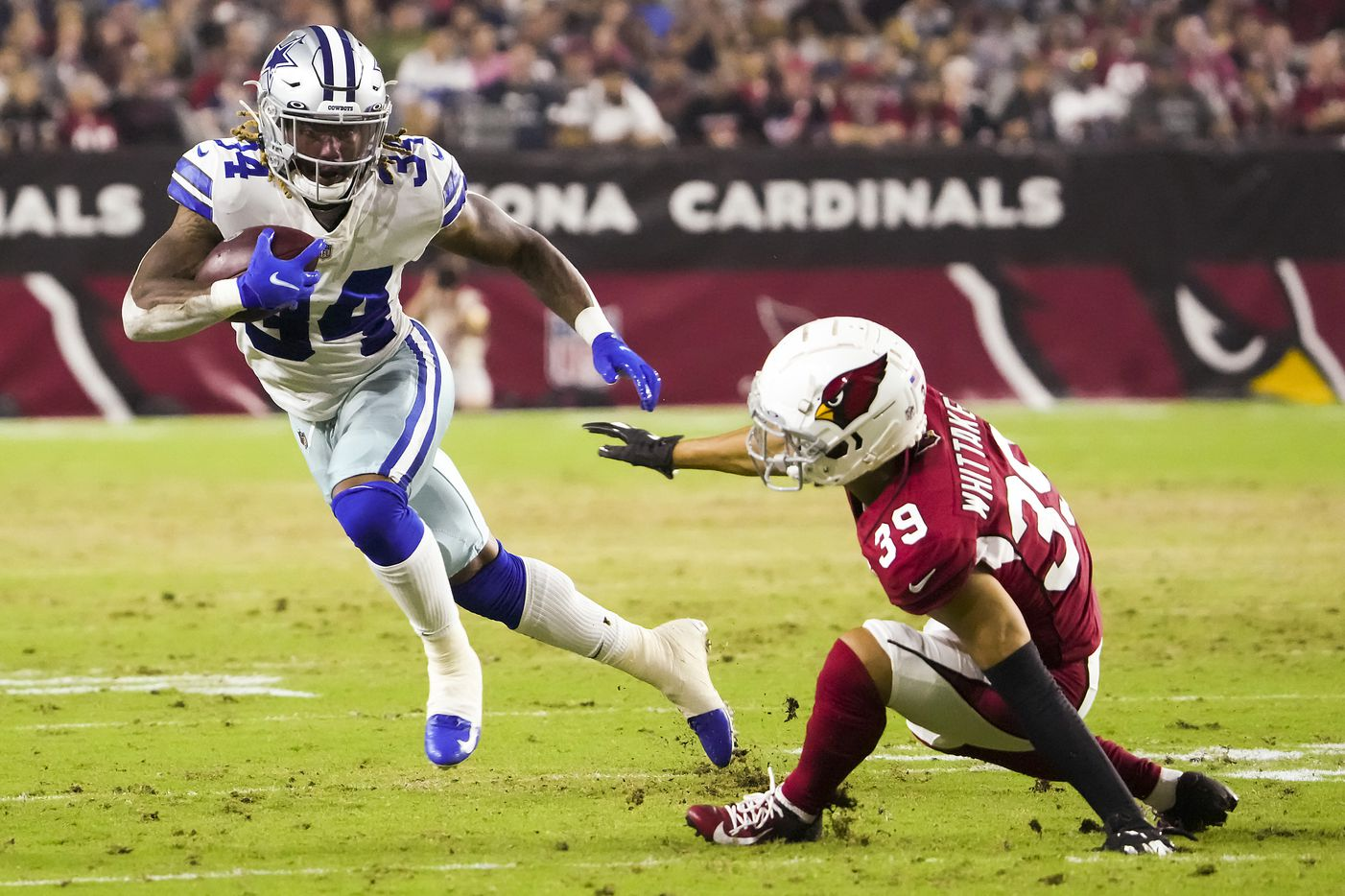 Dallas Cowboys running back Rico Dowdle (34) gets past Arizona Cardinals cornerback Jace Whittaker (39) during the first quarter of an NFL football game at State Farm Stadium on Friday, Aug. 13, 2021, in Glendale, Ariz.