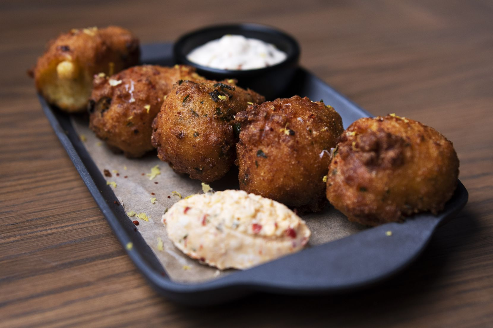 East Texas hush puppies with charred okra, pimento cheese and cajun remoulade sauce are on the menu at Elm & Good restaurant in Deep Ellum.