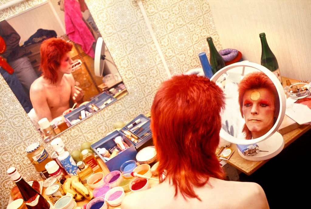 David Bowie uses a mirror to apply makeup in Scotland in 1973.