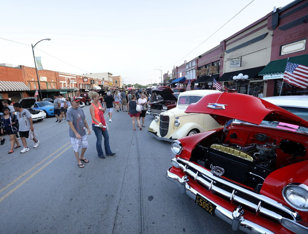 Guests stroll past classic cars on display during the Bluegrass on Ballard festival in Wylie ib June 30, 2018. (Jason Janik/Special Contributor)