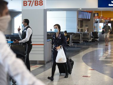 A flight attendant walked the concourse with her bags in Terminal B at DFW International Airport on July 23, 2020.