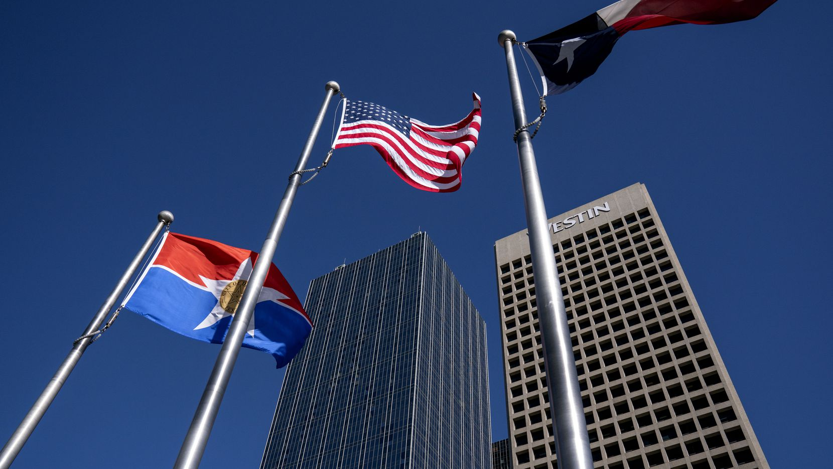The flags of the City of Dallas, United States and Texas fly in front of Renaissance Tower in downtown Dallas.