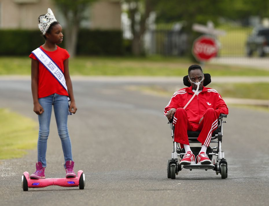 He in his wheelchair, she on her hoverboard - Alana Dixon and her father Rickey Dixon take a stroll in their Red Oak, Texas, Sunday, April 9, 2017.