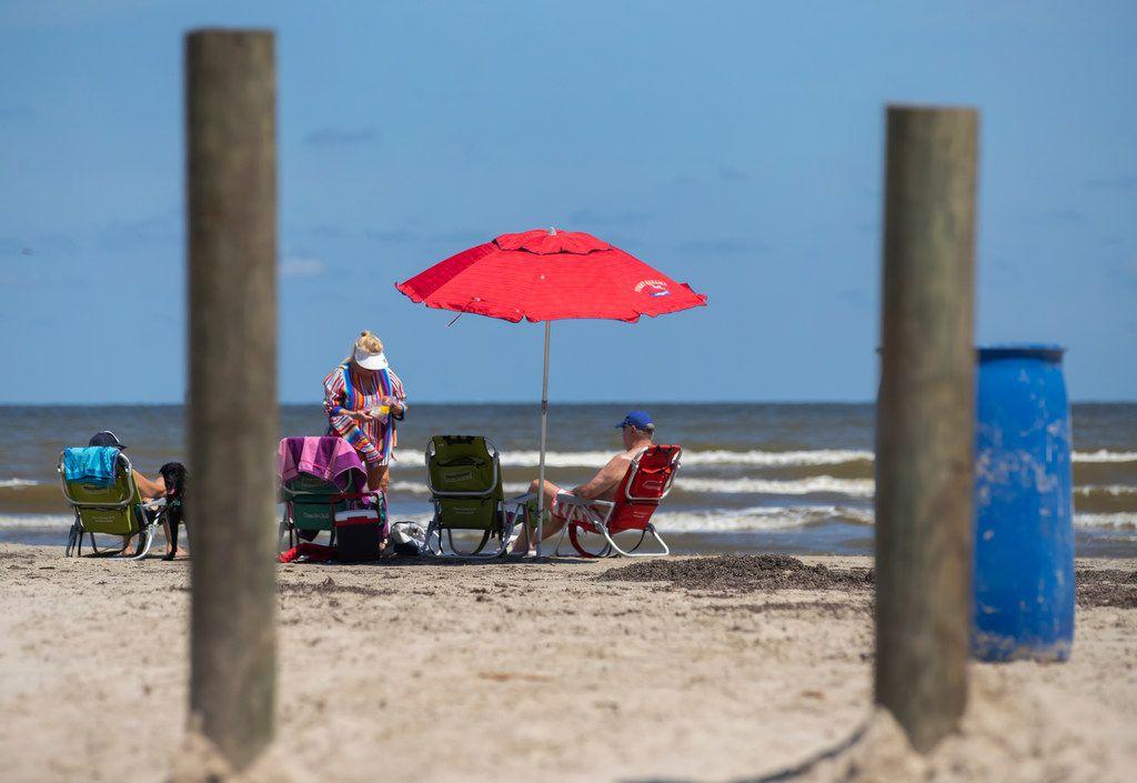 Beachgoers relax near the beach access point on Buccaneer Boulevard in the Pirates Beach community on Galveston's west end in Texas. (Stuart Villanueva/The Galveston County Daily News via AP)