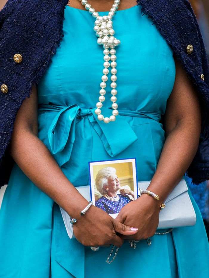 A woman wears pearls and carries a photo of Barbara Bush as she and other guests leave after viewing the casket of former first lady Barbara Bush on Friday, April 20, 2018 at St. Martin's Episcopal Church in Houston. Bush died on Tuesday and her funeral services are on Saturday. (Ashley Landis/The Dallas Morning News)