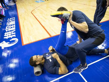 Dallas Mavericks forward Dwight Powell stretches before an NBA China Games 2018 preseason basketball game against the Philadelphia 76ers at Mercedes-Benz Arena on Friday, Oct. 5, 2018, in Shanghai.