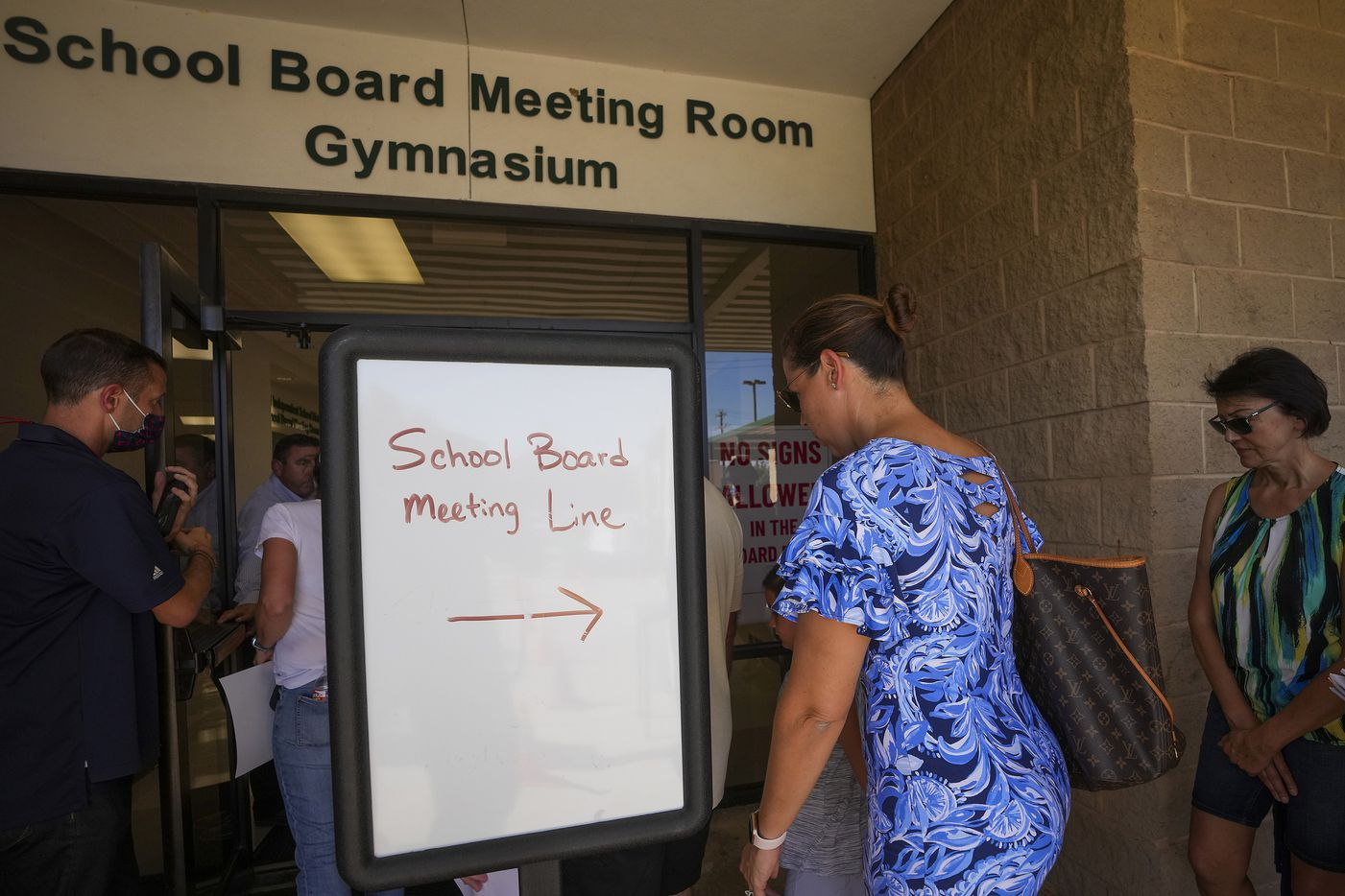 People enter the Carroll ISD school board meeting on Monday, Aug. 23, 2021, in Southlake, Texas. (Smiley N. Pool/The Dallas Morning News)