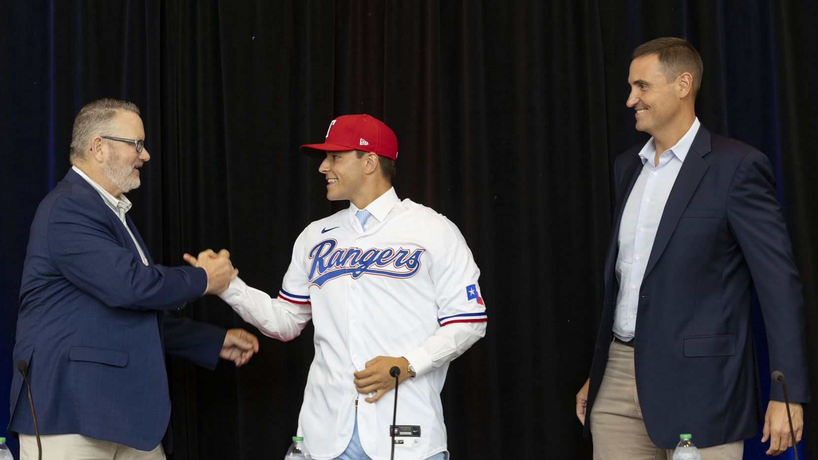 Kip Fagg (left), Texas Rangers Senior Director of Amateur Scouting, Chris Young (right), Rangers Executive Vice President and General Manager, congratulate Jack Leiter from Vanderbilt University after putting on his Texas Rangers jersey following the announcement of his signing on Tuesday, July 27, 2021, at Globe Life Field in Arlington. Leiter was the club's 2021 MLB Draft first round selection and the draft's second overall pick.