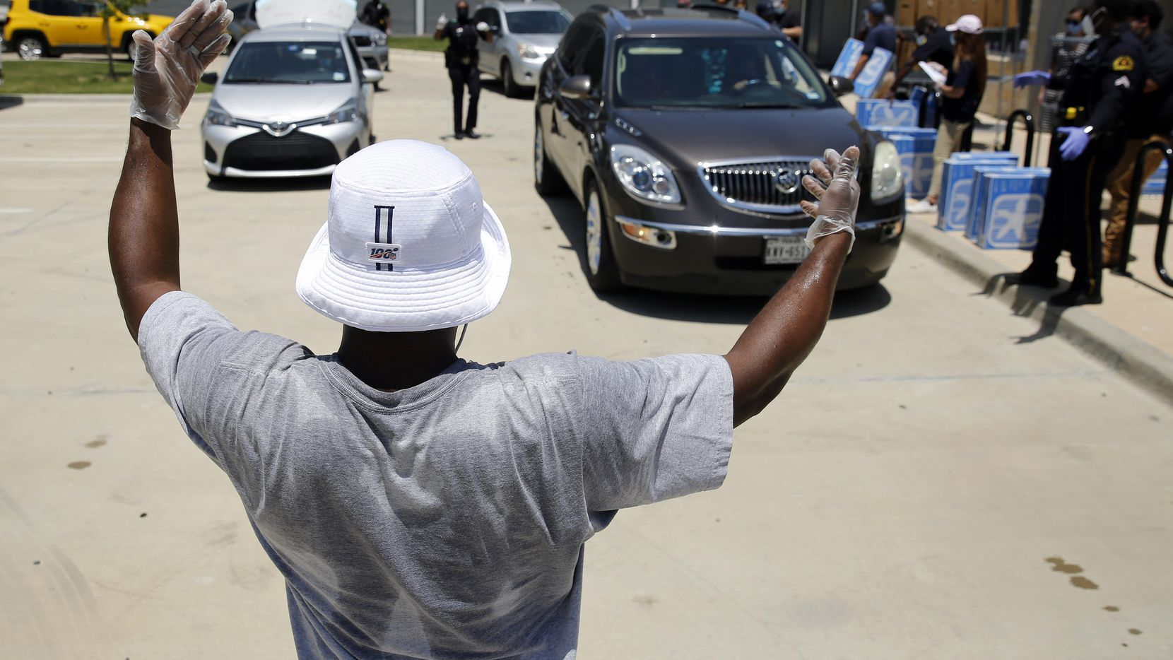 Former Dallas Cowboys player Raghib 'Rocket' Ismail directs traffic as Dallas Police officers help hand out food, fans and PPE to families at the Salvation Army's Pleasant Grove Community Corps Community in Dallas, Thursday, July 16, 2020. Joining him were Dallas Police officers, Salvation Army and Reliant volunteers. The event helped raise awareness about the services available to families in North Texas at 13 different centers.