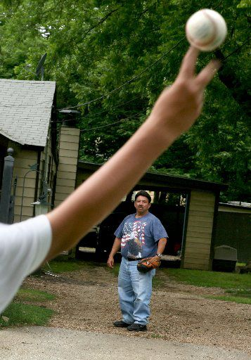 In this 2008 photo, Tony Carrillo stands in his driveway on Parvia Street in La Bajada awaiting a throw from his son, Marcos, 14, across the street Thursday, May 16, 2008 in Dallas. Carrillo is running for City Council in West Dallas.