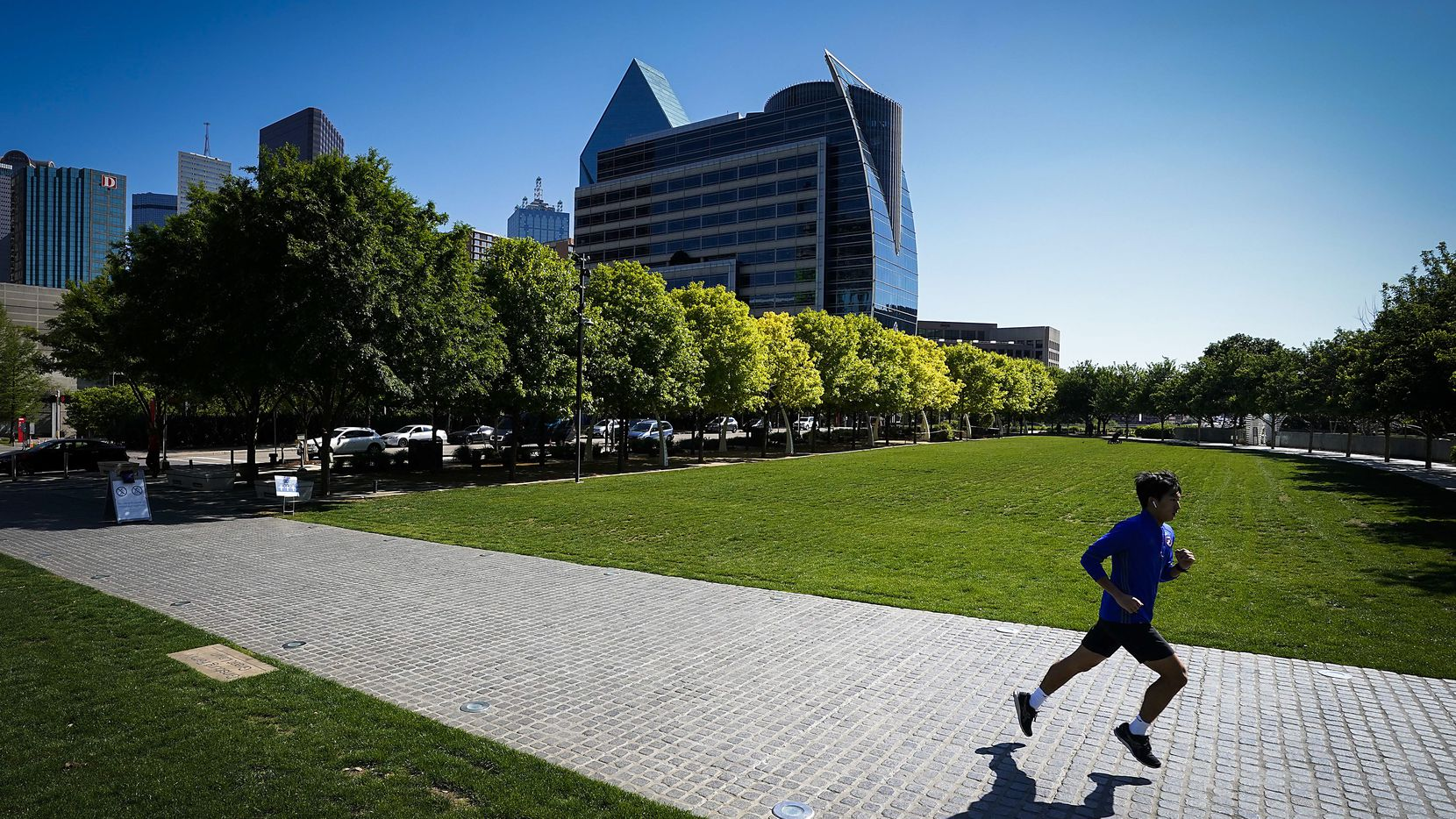 A runner has room to glide through the relatively empty Klyde Warren Park on Monday afternoon, April 13, 2020, in Dallas.