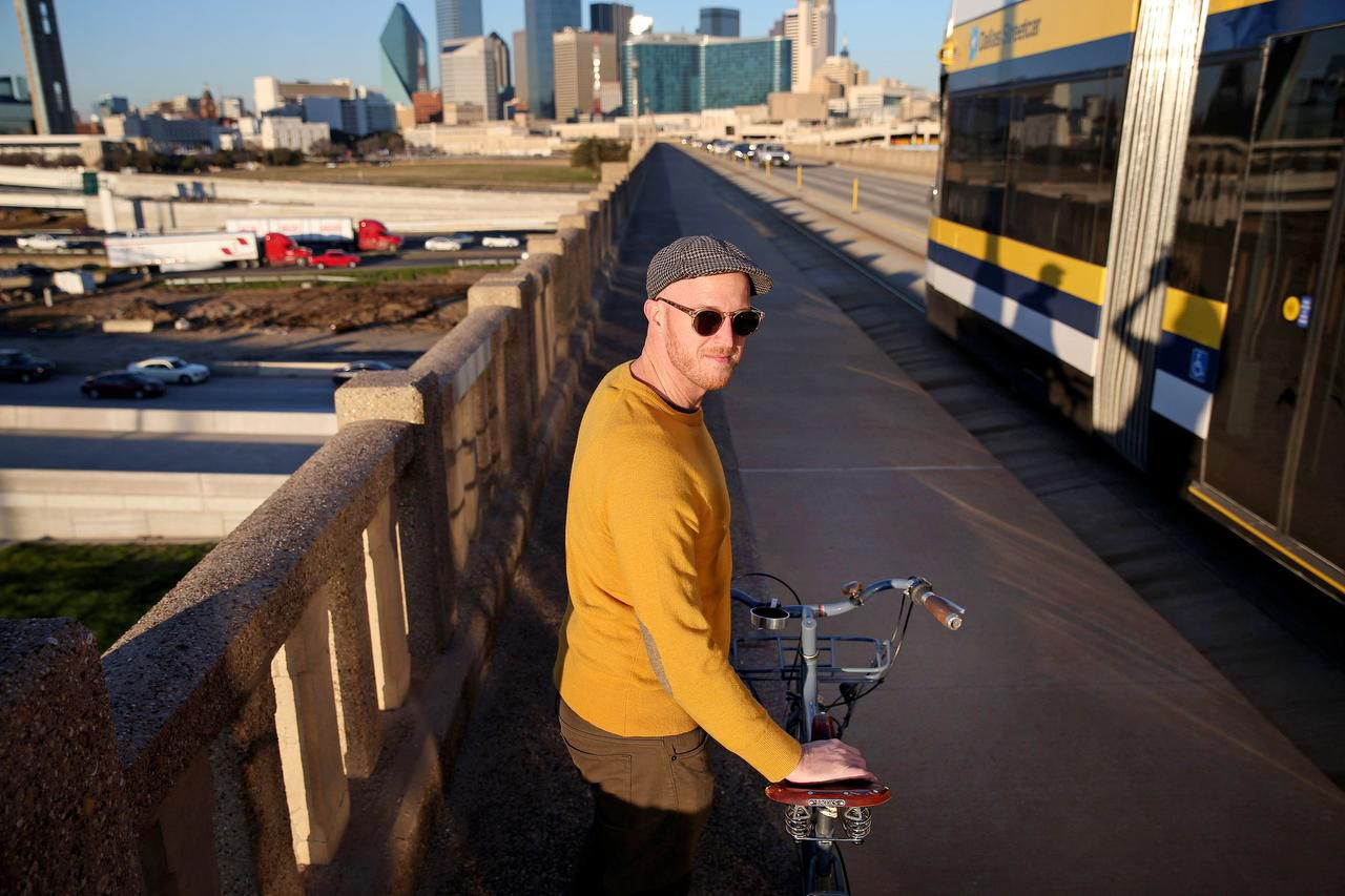 Jason Roberts, co-founder of Bike Friendly Oak Cliff, says Dallas is slowly getting more bicycle-friendly, including adding some bike-dedicated lanes. Here he's on the Houston Street viaduct  headed downtown as a Dallas streetcar passes by at rush hour.