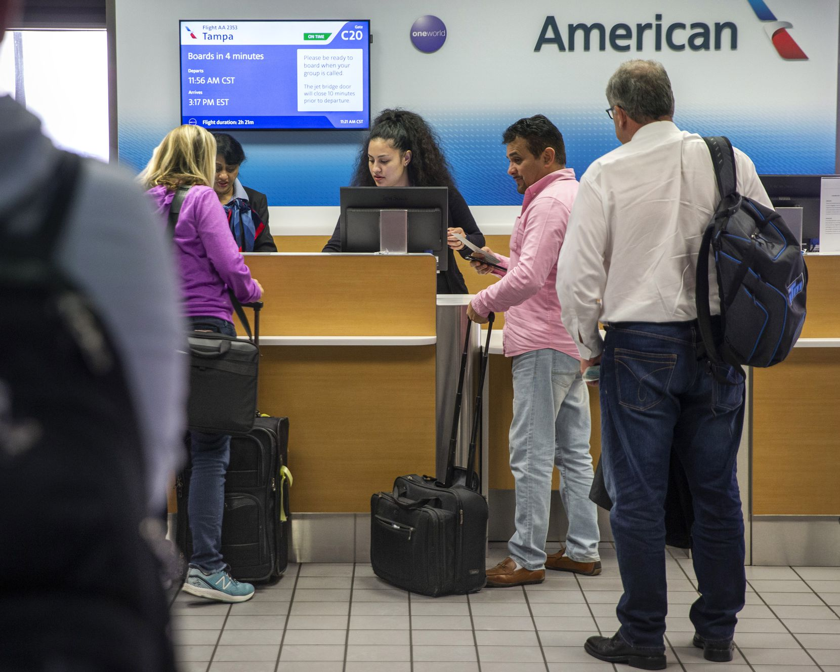 Passengers line up at an American Airlines ticket counter at DFW International Airport in Irving on Nov. 22, 2019. American Airlines is bumping passengers from overbooked flights at an industry-leading rate.