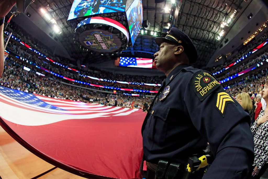 A member of the Dallas Police Department holds an American flag during the national anthem before the championship game of the 2017 NCAA Women's Final Four at American Airlines Center.