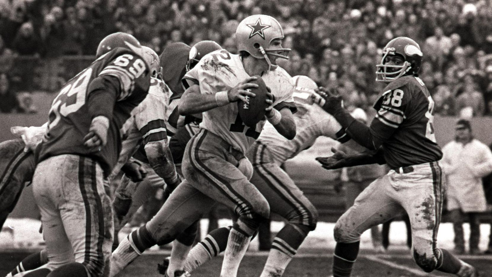 Cowboys quarterback Roger Staubach (12) scrambles for yardage during the final minutes of the Cowboys playoff victory over the Minnesota Vikings in their famous playoff game on 1/8/1975 in the Met Stadium in Minneapolis. Staubach also threw his famous 'Hail Mary Pass' to Drew Pearson (not pictured) in this contest.